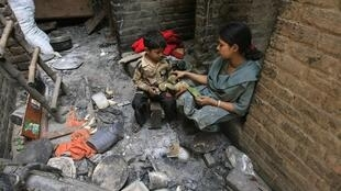 Une mère et son fils, dans les restes de leur maison calcinée du quartier chrétiens de Lahore, ce dimanche 10 mars.