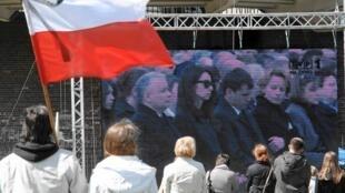 Jaroslaw Kaczynski (gauche), le frère jumeau du président défunt et Marta, sa nièce (à sa droite) filmés sur grand écran pendant les cérémonies d'hommage aux victimes du crash de l'avion présidentiel le 17 avril 2010, à Varsovie.