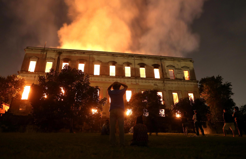 La gente mira como arde el Museo Nacional de Brasil, en Río de Janeiro, el 2 de septiembre de 2018.