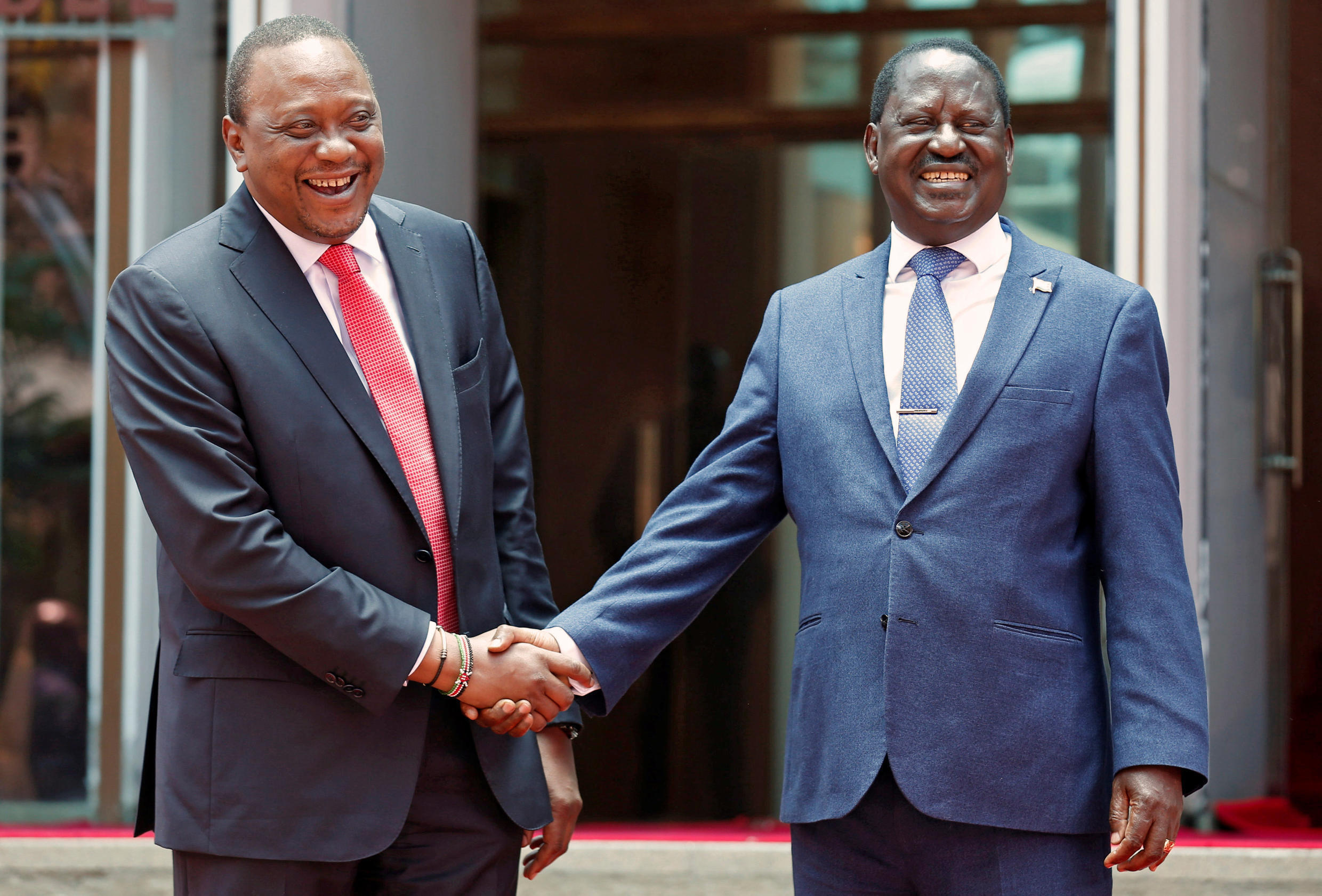 Kenya's President Uhuru Kenyatta (L) greets opposition leader Raila Odinga of the National Super Alliance (NASA) coalition after addressing a news conference at the Harambee house office in Nairobi, Kenya March 9, 2018.