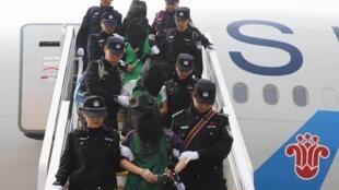 Cảnh sát áp giải một nhóm người bị buộc tội lừa đảo về Trung Quốc, sau khi bị trục xuất khỏi Kenya. Ảnh chụp ngày 13/04/2016 tại sân bay Bắc Kinh