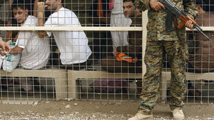 File picture dated April 29, 2010 shows an Iraqi soldier standing guard in front of prisoners waiting to be released from Al-Rusafa detention facility in Baghdad.