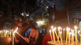 Des pèlerins allument des sièges dans l'église de la Nativité à Bethléem, le 23 décembre 2014.