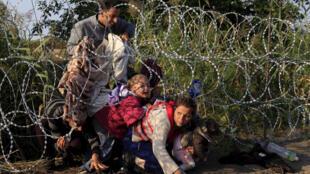 Des migrants traversent la frontière entre la Hongrie et la Serbie en passant sous des barbelés. (photo d'archive)