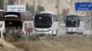 Des bus attendent à l'entrée d'Harasta, dans la Ghouta orientale, pour évacuer les combattants rebelles et leurs familles, le 22 mars 2018.