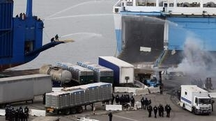 Workers use a water canon against French police launching an operation on the Kalliste car ferry, 10 March 2011