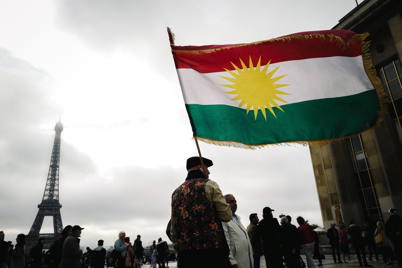 Un homme tient un drapeau kurde lors d'une manifestation sur la place des Droits de l'homme à Paris, le 12 octobre 2019.