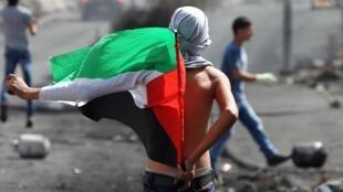 Un homme tient un drapeau palestinien lors d'affrontement avec les forces de sécurité israélienne, près de la colonie de Beit El, le 13 octobre 2015.