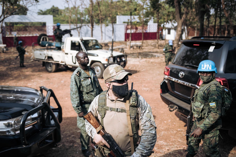 Un casco azul ruandés de la Minusca (d), un guardia ruso de un grupo de seguridad privado (c) y un miembro de la guarda presidencial centroafricana (g) trabajan en la protección del presidente Faustin Archange Touadéra el 27 de diciembre de 2020 en Bangui