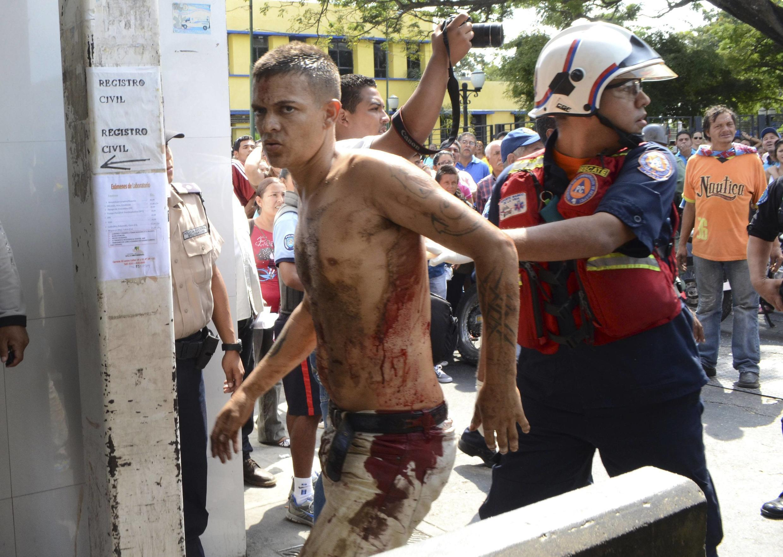 Equipes de socorro transferem feridos após rebelião na prisão de Ubirana, na Venezuela.