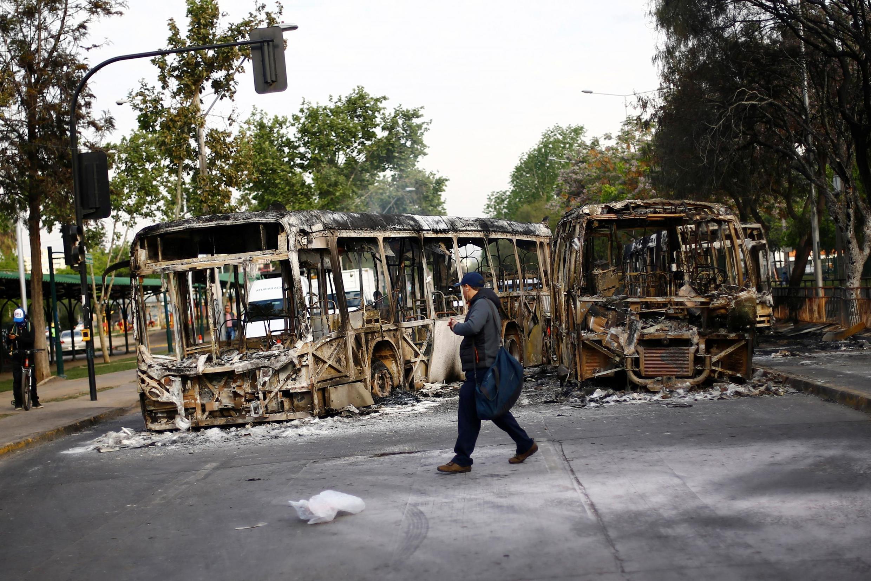 Um homem caminha na frente de dois ônibus incendiados após um protesto contra o aumento dos preços das passagens de metrô em Santiago, Chile, 19 de outubro de 2019.