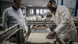 """Constantini (left) and Frederique cut the freshly-made laurel soap """"made in France"""" at the Alepia factory"""