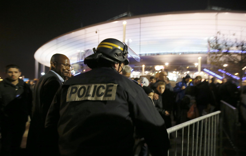 Болельщики покидают «Стад де Франс» под контролем полиции 13 ноября 2015 г.