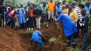 Des travailleurs burundais de la CVR creusent pour extraire des corps d'une fosse commune sur la colline de Bukirasazi dans la province de Karusi, le 27 janvier 2020.