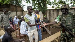 Un habitant du quartier PK5 remet sa machette à un soldat de la Misca. Bangui, le 8 juin 2014.