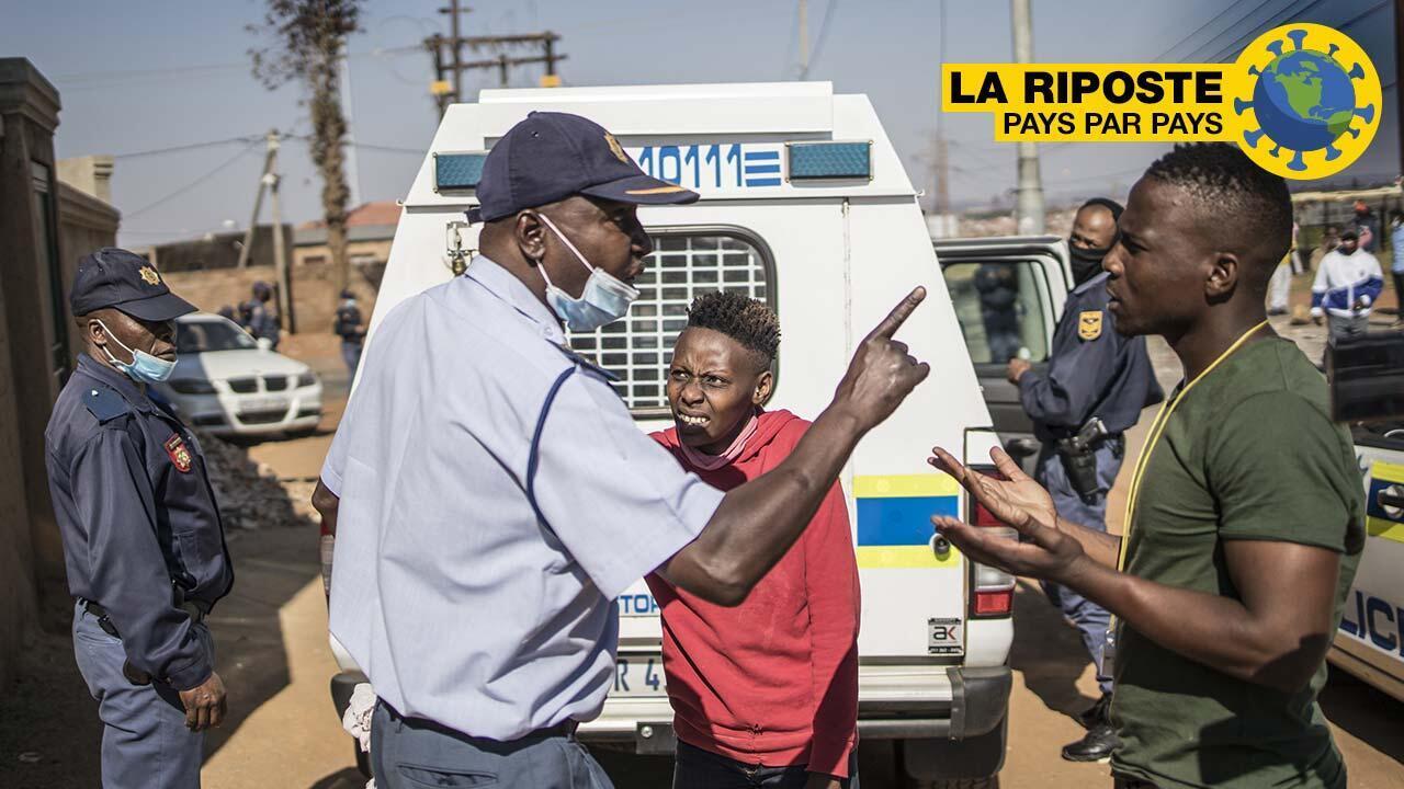 Un policier sud-africain se dispute avec un homme demandant la libération d'un manifestant arrêté pour avoir bravé le confinement à Snake Park, à Soweto, le 13 mai 2020.