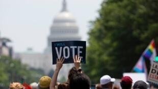 """Manifestante exibindo um cartaz """"Eu vou votar"""" junto da sede do Congresso em Washington."""