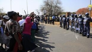 Policiais sul-africanos vigiam a chegada nesta segunda-feira de alguns dos 250 mineiros presos na semana passada após conflito.