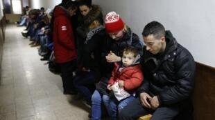Arrêtés pour avoir tenté de traverser la frontière vers l'Hongrie, des Kosovars attendent dans un poste de police à Subotica en Serbie.