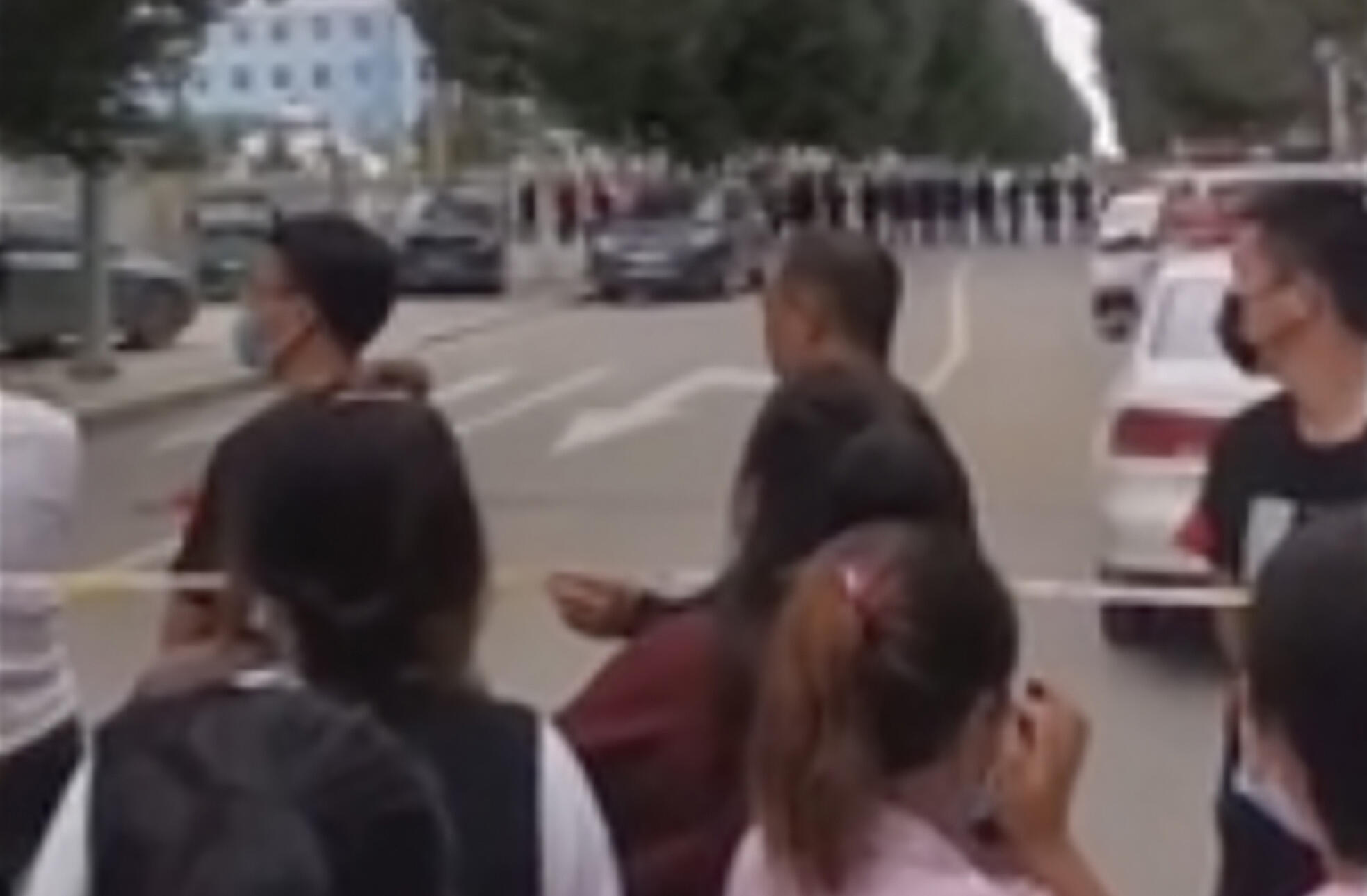 In this image made from video taken in August 2020, parents gather behind a police line outside a school in Tongliao in Northwestern China's Inner Mongolia region. Ethnic Mongolians, including students and parents, in China's Inner Mongolia region are demonstrating their anger in rare public protests against a new bilingual education policy that they say is endangering the Mongolian language.