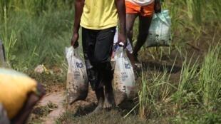 À Abuja, les gens emportent des sacs portant l'inscription «—CaCovid / Ne pas vendre—», lundi 26 octobre 2020.