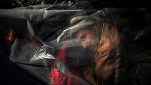 Un homme réfugié faisant partie de la caravane cherchant à atteindre les États-Unis se réveille sous une bâche à Tijuana, au Mexique, le 16 novembre 2018.