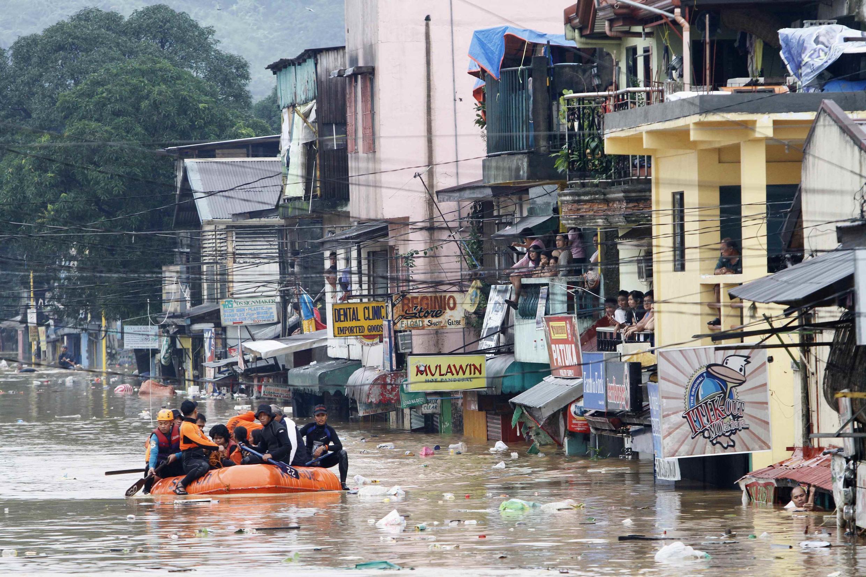 Lực lượng cứu hộ cố giúp cư dân bị lụt, nhưng nhiều người vẫn không chịu sơ tán. Ảnh chụp ngày 09/08/2012 tại một ngôi làng ở Marikina City, vùng Manila.