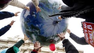Ảnh minh hoạ. Những người biểu tình tung một quả địa cầu lên cao ngay trước khi hội nghị về khí hậu Paris 2015 bắt đầu.