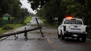 Une voiture de police contourne un pylône électrique arraché au passage de l'ouragan Irma, le 7 septembre 2017, à Nagua, en République dominicaine.