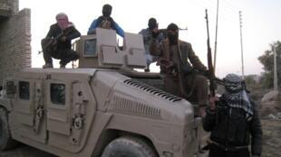 Des sunnites irakiens armés posent sur un véhicule de l'armée, à Faloudja, le 9 janvier 2014.