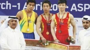 O ginasta brasileiro Sérgio Sasaki sobe ao pódio em Doha, ao lado de atletas chineses.