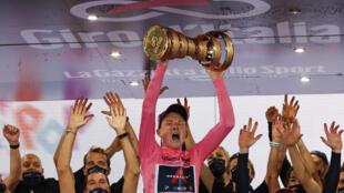 El ciclista británico Tao Geoghegan Hart, del equipo Ineos, celebra en el podio después de la 21ª y última etapa del Giro de Italia, disputada entre Cernusco  Naviglio y Milán el 25 de octubre de 2020