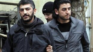 O fotógrafo da agência France-Presse Mustafa Ozer (e) é acompanhado pela polícia civil turca, em Istambul, nesta terça-feira.