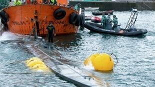 A Spanish Guardia Civil's diver stands over the refloated prow of a submarine used to transport drugs illegally in Aldan, northwestern Spain, on November 26, 2019.
