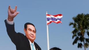 Une jeune fille pose au côté de l'effigie de Prayuth Chan-ocha lors de la Journée des enfants au siège du gouvernement à Bangkok.