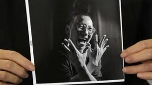 A photograph of Chinese dissident Liu Xiaobo is held by his wife Liu Xia during an interview in Beijing
