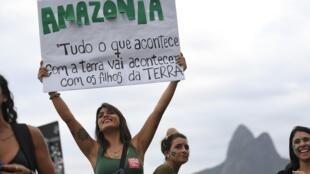 """Ativista segura cartaz com a advertência: """"Tudo o que acontece com a Terra vai acontecer com as crianças da Terra"""", na praia de Ipanema, no Rio de Janeiro, no dia 25 de agosto."""