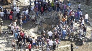 Moradores de Tripoli, no Líbano, observam a cratera provocada pelas duas explosões nas mesquitas da cidade, em foto do dia 23 de agosto de 2013.