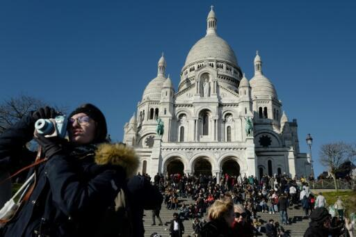 Tourists throng the steps outside the Sacre Coeur basilica in Paris' iconic Montmartre district, an area at risk of being swamped by mass tourism