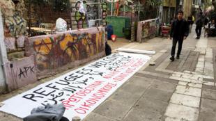 Une banderole en soutien aux réfugiés finit de sécher rue Tsamadou, à Athènes.