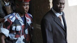 Le général Brunot Dogbo Blé (D) quitte le tribunal militaire escorté par des gendarmes. Abidjan, le 2 octobre 2012.