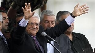 O presidente palestino Mahmoud Abbas acena para a multidão em Ramallah