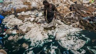 Aux abords du Lac Victoria, un homme lave des sacs plastique dont le colorant bleu va polluer les eaux.