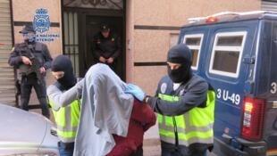 Un hombre detenido es escoltado por la policía española.