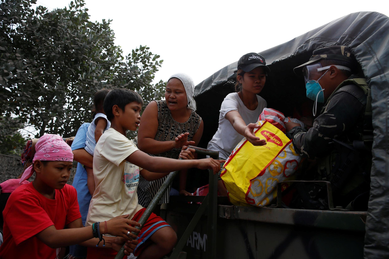 Un soldat aide à évacuer des résidents vers un centre après l'erruption du volcan à Guniobatan, dans la province d'Albay, le 23 janvier 2018.