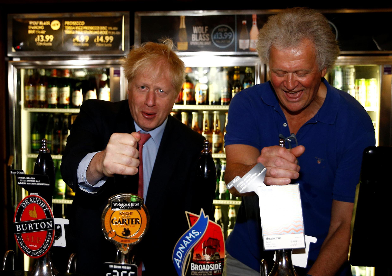 Boris Johnson, alors candidat au poste de Premier ministre, en campagne le 10 juillet dernier au Wetherspoons Metropolitan Bar de Londres avec le patron des lieux, Tim Martin.