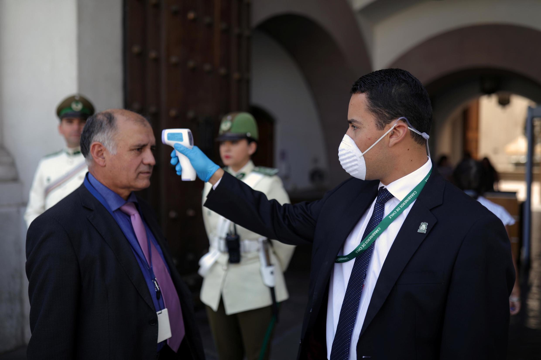 Agentes de segurança controlam acesso na entrada do palácio presidencial em Santiago. 18/03/2020