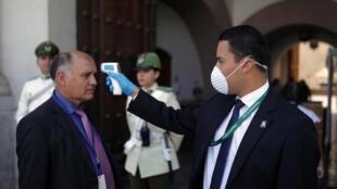 Los agentes de seguridad controlan el acceso a la entrada del palacio presidencial en Santiago. 18/03/2020