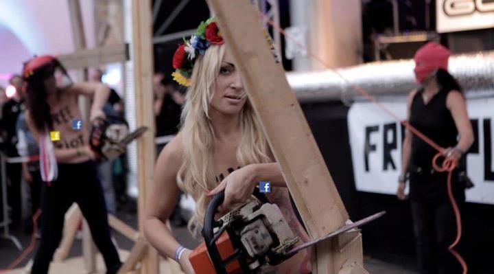Активистка Femen Инна Шевченко спиливает крест на фестивале в Голландии