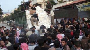 L'Armée syrienne libre distribue l'aide alimentaire reçue du Croissant rouge, près d'Idleb, le 28 octobre 2012.